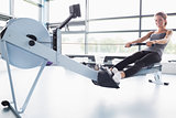 Smiling woman training on row machine