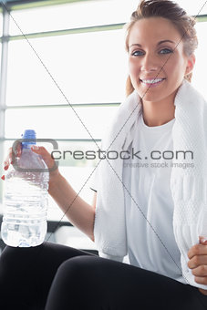 Woman with towel around her neck drinking water