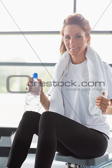 Woman sitting on a row machine and drinking water