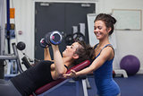 Female trainer teaching woman lifting weights