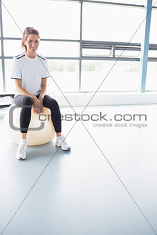 Woman smiling while sitting on exercise ball