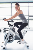 Smiling woman training on exercise bike