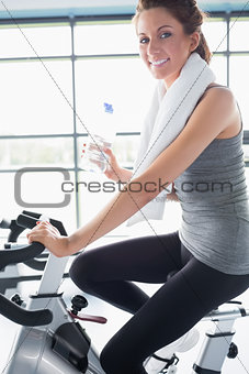 Woman riding an exercise bike and drinking water