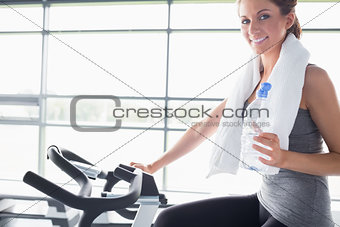 Woman holding a bottle and riding an exercise bike