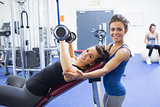 Smiling woman lifting weights and trainer