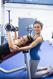 Happy woman lifting weights and her trainer