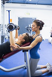 Concentrated trainer teaching woman lifting weights
