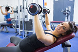 Cheerful woman lifting weights