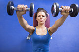 Woman energetically lifting weights