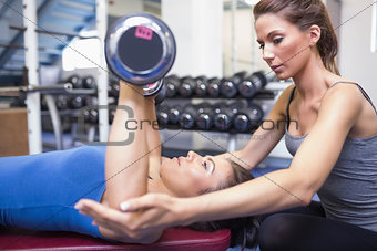 Woman lifting weights with trainer