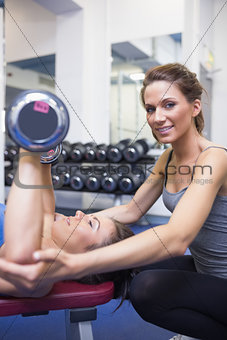 Trainer smiling with woman lifting weights