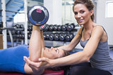 Happy trainer with woman lifting weights