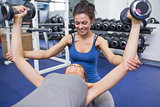 Trainer teaching woman lifting weights