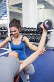 Woman lifting weights with her trainer