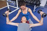 Cheerful trainer helping woman lifting weights