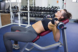 Woman training with weights while lying