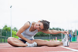 Smiling woman stretching on a track