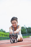 Smiling woman stretching on track