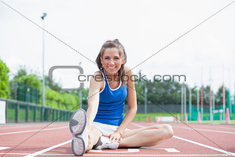 Cheerful woman stretching her leg