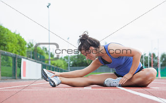 Woman stretching in a stadium