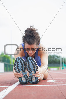Woman stretching out on a track