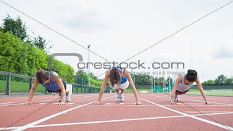 Three women stretching on running track