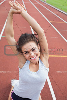 Woman on a track stretching her arms