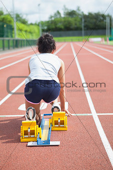 Woman at starting blocks on track