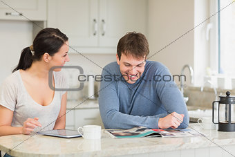 Two people sitting in the kitchen and chatting