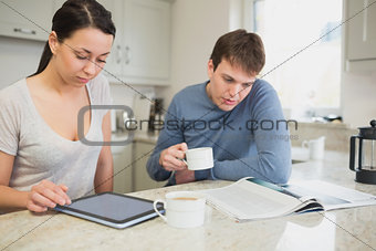 Two people reading from tablet pc and newspaper