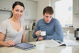 Two people sitting in the kitchen with tablet pc and newspaper