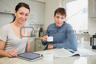 Smiling woman with tablet pc and man with newspaper