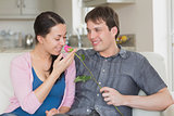 Man presenting flower to girlfriend