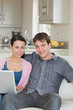 Young couple relaxing while using the laptop
