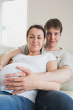 Pregnant woman lying on couch with partner