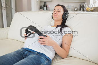 Pregnant woman holding headphones to belly and listening to music