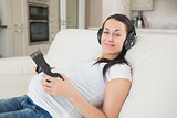 Prospective mother lying on the couch listening to music and holding headphones to belly
