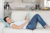 Pregnant woman reading on couch