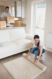 Woman laying out rug with man holding moving boxes