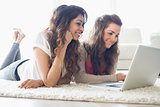 Two women relaxing at laptop