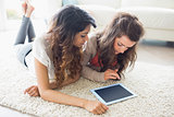 Two women looking at tablet pc on floor