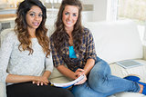 Two women sitting on a couch while writing on a notepad