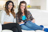 Two girls sitting on a couch with notepad and tablet pc