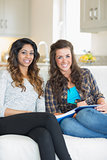 Two smiling girls sitting on a couch while writing on a notepad