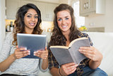 Smiling girls reading a book and holding a tablet computer