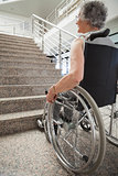 Elderly lady in wheelchair looking up stairs