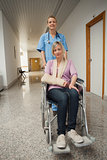 Nurse pushing wheelchair of patient with arm sling