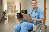 Smiling nurse in a wheelchair holding a folder