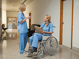 Nurse with drink talking to nurse in wheelchair with folder
