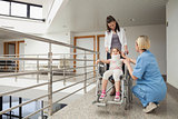 Nurse talking with child in wheelchair and neck brace with mother